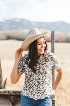 A lady modeling a snap cotton blouse in a white cowboy hat.