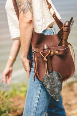 A close up of a lady modeling a handmade leather garden tool belt.